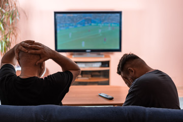 Father and son watching football or soccer on a TV.