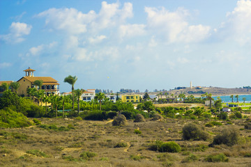 Landscape of town Paphos with houses, trees and lighthouse in background against blue sky, Cyprus