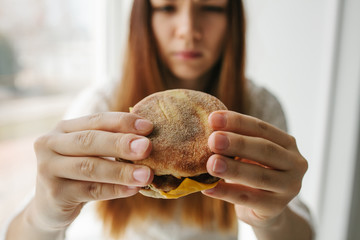 A young girl shows that she does not like a burger. Conceptual image of refusal from unhealthy eating.