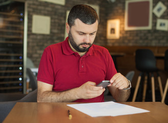 Handsome young man taking photo of documents with smartphone