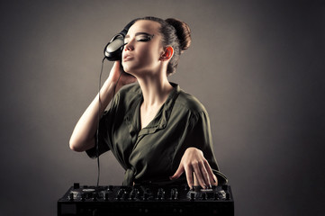 charming girl behind DJ remotes in headphones