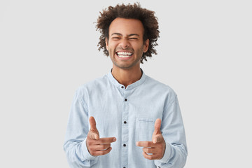 Positive mixed race male startup owner rejoices success, points at camera, has broad smile, being in high spirit, dressed in casual shirt, stands at studio. Confident student happy to graduate