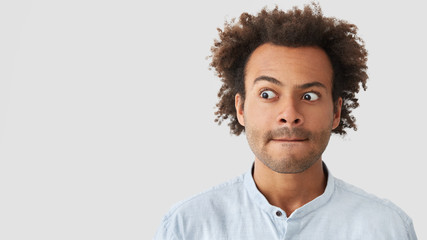 Studio shot of embarrassed mixed race male looks with surprisement aside, keeps lips pressed, has Afro hairstyle, stubble, stands against white background with blank space, being deep in thoughts