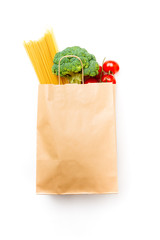 Photo of paper bag with broccoli, spaghetti and tomatoes