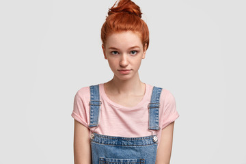 Studio shot of serious foxy female teenager look confidenlty, listens attentively friend, analyzes information in mind, wears casual clothes, has freckled skin, isolated over white background