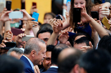 Turkish President Tayyip Erdogan poses for photographs as he leaves a polling station in Istanbul