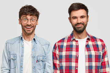 Two male companions with beards, stand next to each other, have joyful expressions, satisfied after spending evening watching football match, wears fashionable shirts, pose against white wall