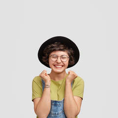 Joyful European female in black hat and denim dungarees, clenches fists and has broad smie, being in high spirit after successful day, poses against white background. People and happiness concept