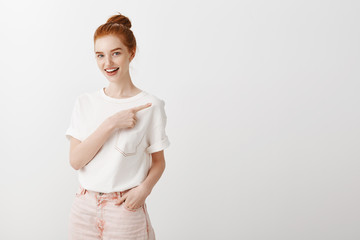 Intrigued charming stylish woman with red hair in bun hairstyle, pointing at upper right corner and smiling broadly at camera, asking question, being interested in price of cute t-shirt in shop