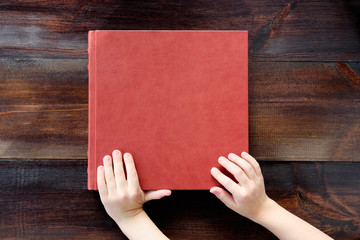 kid holding hands on brown leather covered wedding album or book