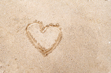 Heart drawn in the sand on the Beach background. Top view photo and space for text, love and valentine day concept
