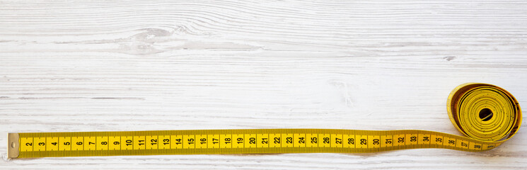 Yellow measuring tape on white wooden table, top view. From above, flat lay. Copy space.