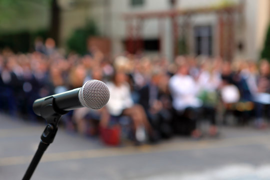 Microphone and stand in front of graduation ceremony audience against a background of auditorium
