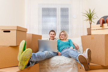 Photo of man with laptop and woman sitting on sofa among cardboard boxes