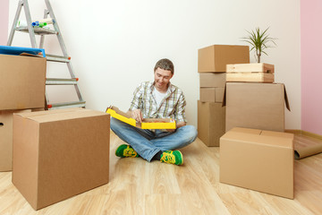Photo of man sitting on floor with pizza among cardboard boxes
