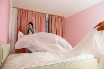 Image of young woman covering bed with polyethylene