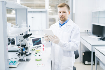 Young male microbiologist in laboratory coat standing at desk with microscope and green vegetable samples and holding tablet smiling and looking at camera