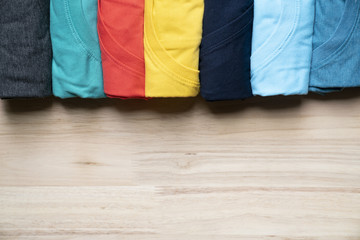 close up of rolled colorful clothes on table background
