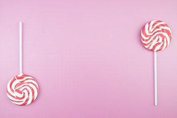 Flat lay top view tasty appetizing concept, minimal Sweet Treat Swirl Candy Lollipop marshmallow Colorful pattern on pink pastel background and copy space.