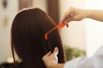 Stylist combing woman hair at salon