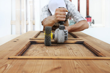 carpenter work the wood with the sander grinding electric tools for rustic renovate