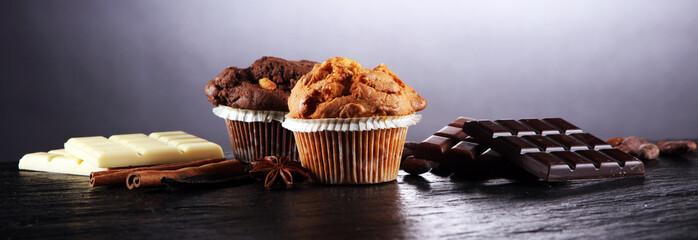 Chocolate muffin and nut muffin, homemade bakery on dark background.