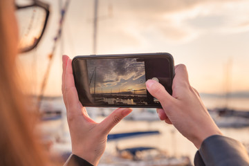 Girl takes photo of harbor with yachts on smartphone at sunset. Travel, photography theme.