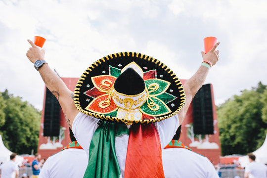 Mexican fans in uniform and sombrero are happy for their team during the World Cup