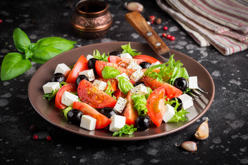 Salad with tomatoes, feta, olives and Basil, serving on a dark background