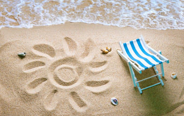 Deckchair on a beach with a sun drawn on the sand