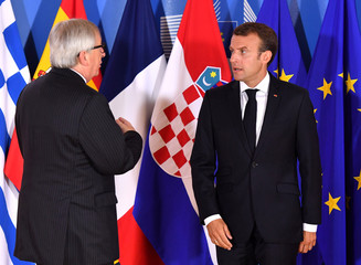 European Commission President Jean-Claude Juncker speaks with French President Emmanuel Macron during an informal EU summit on migration at EU headquarters in Brussels