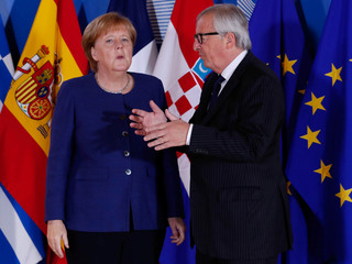 German Chancellor Angela Merkel is welcomed by European Commission President Jean-Claude Juncker at the start of an emergency European Union leaders summit on immigration at the EU Commission headquarters in Brussels