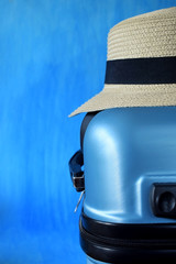 A straw hat on a blue suitcase. Concept of packing for a holiday
