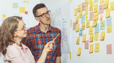 Business people discuss and plan creative work, making notes on paper stickers. A young man and a woman use the post it for new ideas.