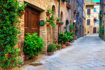 Rustic brick houses decorated with colorful flowers, Pienza, Tuscany, Italy