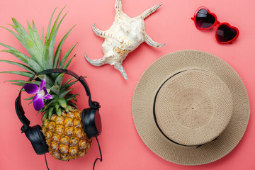 Flat lay objects the accessory for travel summer holiday & music background concept.Table top view of fashion clothing to traveler at beach.Hat & pineapple listen radio with item on modern pink paper.