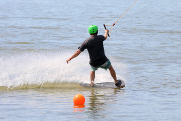 A young man kiteboarding / surfing / wakeboarding holding the rope with one hand