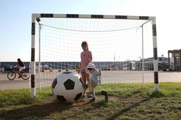 A child kicks a giant ball near the Olympic Park in Sochi
