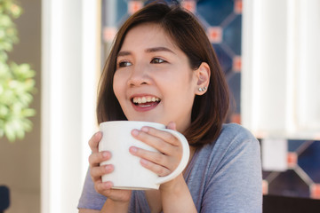 Portrait of happy young asian business woman with mug in hands drinking coffee in the morning at cafe. Asian women express emotion relax at the cafe or coffee shop. Woman food and drink cafe concept.