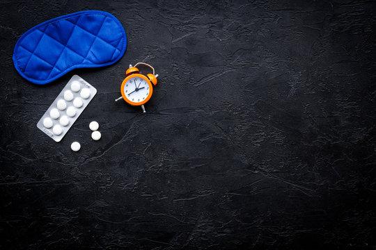 Medicine helps get asleep. Good sleep. Sleeping pills near sleeping mask and alarm clock on black background top view copy space