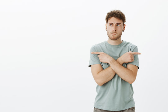 Portrait of confused european male model in earrings, smirking and frowning while thinking, crossing hands and pointing left and right while choosing direction, standing and deciding where to go