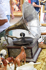 old antique gramophone with a plate on the stall next to ceramic dogs