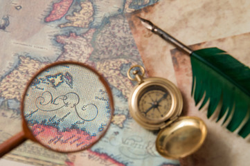 Planning a trip: closeup view of a magnifying glass on an old map with vintage items