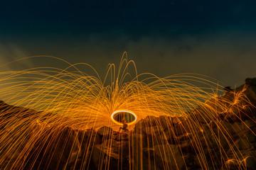 burning steel wool on the mountain rock above lagoon