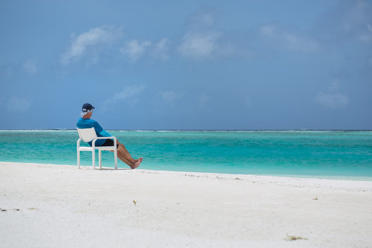 A man sits on a chair on the beach and looks out to sea