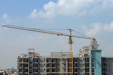 construction site of building condominium with crane above by cloudy