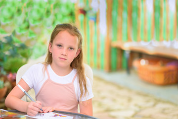 Little freckles girl painting at table in summer garden. Serious kid drawing outdoor and looking at camera. Cute child  doing homework at sunny yard.Copy space for text.