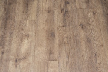 Modern vinyl floor with old wood imitation. Close-up of new beige flooring with texture from tiles with brown grains and knots. Decorative background of wooden boards.