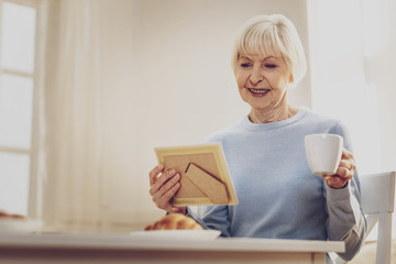 Positive mood. Happy aged woman resting at home while looking at the family