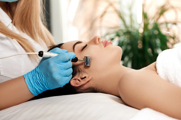 Beautician makes cleaning of face in spa salon.